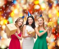 Three smiling women in blue hats with gift boxes Stock Images