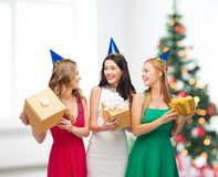 Three smiling women in blue hats with gift boxes Stock Photo