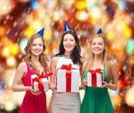Three smiling women in blue hats with gift boxes Royalty Free Stock Image