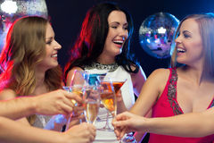 Three smiling women with cocktails in club Royalty Free Stock Photography