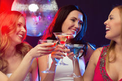 Three smiling women with cocktails and disco ball Royalty Free Stock Photo
