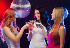 Three smiling women with cocktails and disco ball Stock Photos