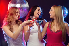 Three smiling women with cocktails and disco ball Royalty Free Stock Photos