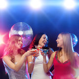Three smiling women with cocktails and disco ball Royalty Free Stock Image