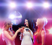 Three smiling women with cocktails and disco ball Stock Image