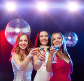 Three smiling women with cocktails and disco ball Stock Images