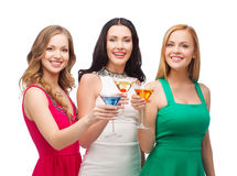 Three smiling women with cocktails Stock Images