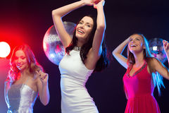 Three smiling women dancing in the club Stock Photos