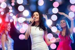 Three smiling women dancing and singing karaoke Royalty Free Stock Photos