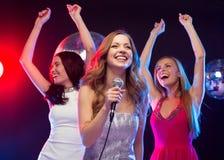 Three smiling women dancing and singing karaoke Royalty Free Stock Image