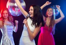 Three smiling women dancing and singing karaoke Stock Images