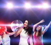 Three smiling women dancing and singing karaoke Stock Photography