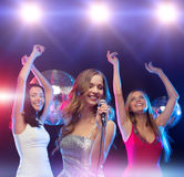 Three smiling women dancing and singing karaoke Stock Image