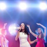 Three smiling women dancing and singing karaoke Stock Image