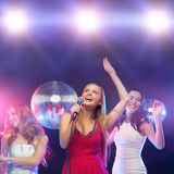Three smiling women dancing and singing karaoke Stock Images