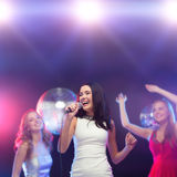 Three smiling women dancing and singing karaoke Stock Photo