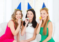 Three smiling women in hats blowing favor horns Stock Image