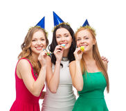 Three smiling women in hats blowing favor horns. Celebration, friends, bachelorette party, birthday concept - three smiling women wearing blue hats and blowing Royalty Free Stock Image