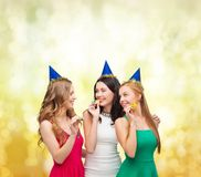 Three smiling women in hats blowing favor horns Royalty Free Stock Photography