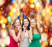 Three smiling women in hats blowing favor horns Stock Photography