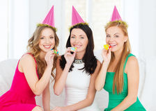 Three smiling women in hats blowing favor horns. Celebration, friends, bachelorette party, birthday concept - three smiling women wearing pink hats and blowing Stock Image