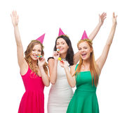 Three smiling women in hats blowing favor horns Stock Photo