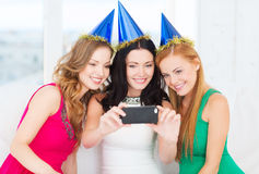 Three smiling women in hats having fun with camera. Celebration, friends, bachelorette party, birthday concept - three smiling women in blue hats having fun with Royalty Free Stock Image