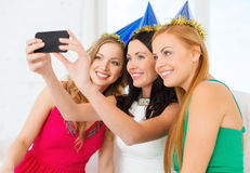 Three smiling women in hats having fun with camera Royalty Free Stock Image