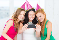 Three smiling women in hats having fun with camera. Celebration, friends, bachelorette party, birthday concept - three smiling women in pink hats having fun with Stock Photo