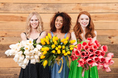 Three smiling women showing bouquets of flowers at camera. Three smiling women in dresses posing near the wooden wall and showing bouquets of flowers at the Stock Photo