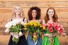 Three smiling women showing bouquets of flowers at camera. Three smiling women in dresses posing near the wooden wall and holding bouquets of flowers which Royalty Free Stock Photos