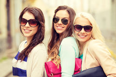 Three smiling women in sunglasses with bags Stock Photography
