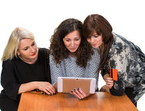 Three smiling women with tablet pc Stock Images