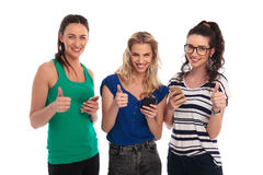 Three smiling women texting on  smartphones make the ok sign Royalty Free Stock Images