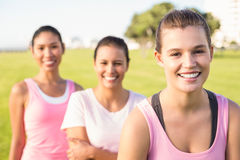 Three smiling women wearing pink for breast cancer. Portrait of three smiling women wearing pink for breast cancer in parkland Royalty Free Stock Images