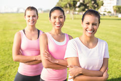 Three smiling women wearing pink for breast cancer Royalty Free Stock Images