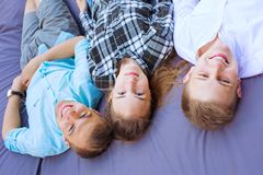 Three smiling young friends laying on a cushion. Image of three happy smiling young friends laying on a big cushion, happiness and friendship concept. Upside royalty free stock photography