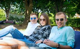 Three smiling young friends relaxing on a cushion outdoors. Image of three young friends in fashionable sunglasses relaxing on a big cushion, happiness and royalty free stock photography