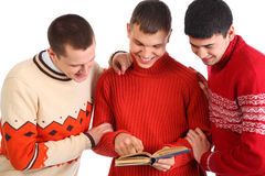 Three smiling young men read book Stock Photos