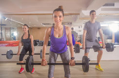 Three smiling young people gym weights bar women man Stock Photos