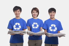 Three smiling young people standing in a row carrying newspapers and wearing recycling symbol t-shirts, studio shot Stock Images