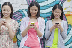 Three smiling young woman standing side by side and texting on their phones in front of a wall with graffiti Royalty Free Stock Photo