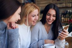 Three smiling young women looking photos at telephone. Side view of three smiling young women looking photos at telephone Royalty Free Stock Image