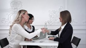 Three smily business women shaking hands in the office. Professional shot on BMCC RAW with high dynamic range. You can use it e.g in your commercial video Royalty Free Stock Images