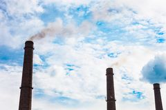 Three smoke stacks of the industrial plant against the cloudy sk Stock Photo