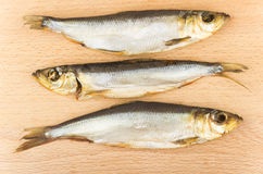 Three smoked fish on board Royalty Free Stock Photos