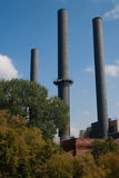 Three Smokestacks. A photograph of three smokestacks rising up from a building Stock Image