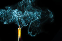 Three smoking Joss sticks Royalty Free Stock Photos