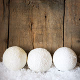 Three snowballs with wooden background Stock Images