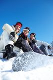 Three snowboarders. Portrait of happy company of guys and girl sitting on snow Stock Photo